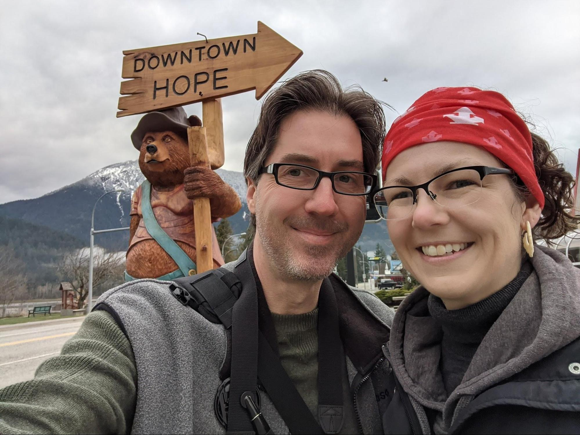woman and man standing in front of a chainsaw carving of a bear wearing blue overalls, a brown hat, and holding a directional sign pointing to downtown Hope.