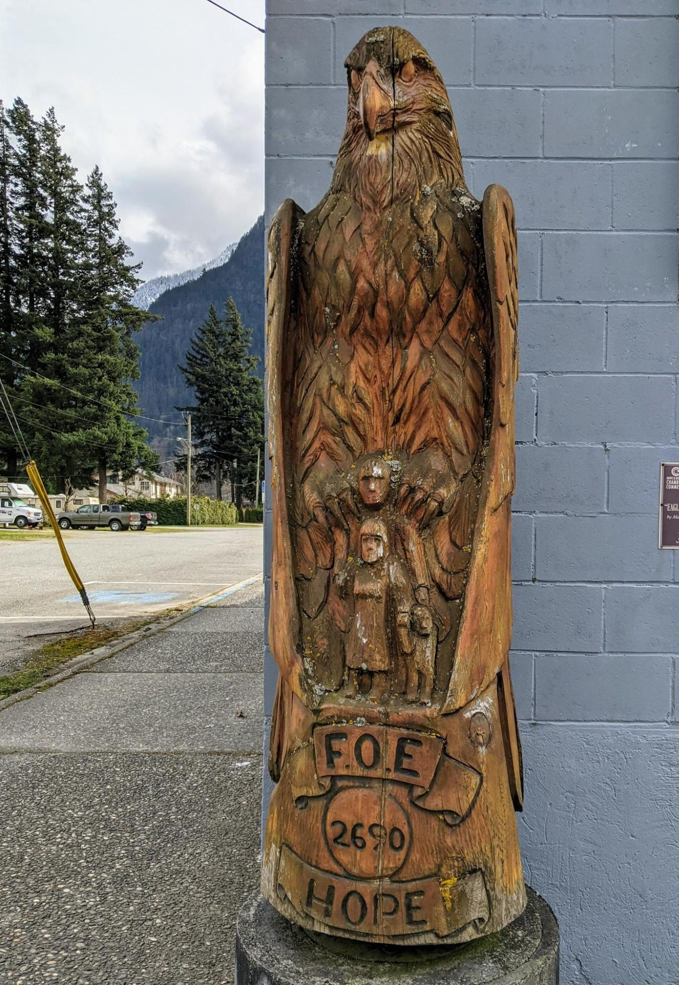 Chainsaw carving by master carver Pete Ryan of a large eagle sitting on a man's shoulders sheltering the man and his family with it's wings. Carving on display in the town of Hope, British Columbia, Canada