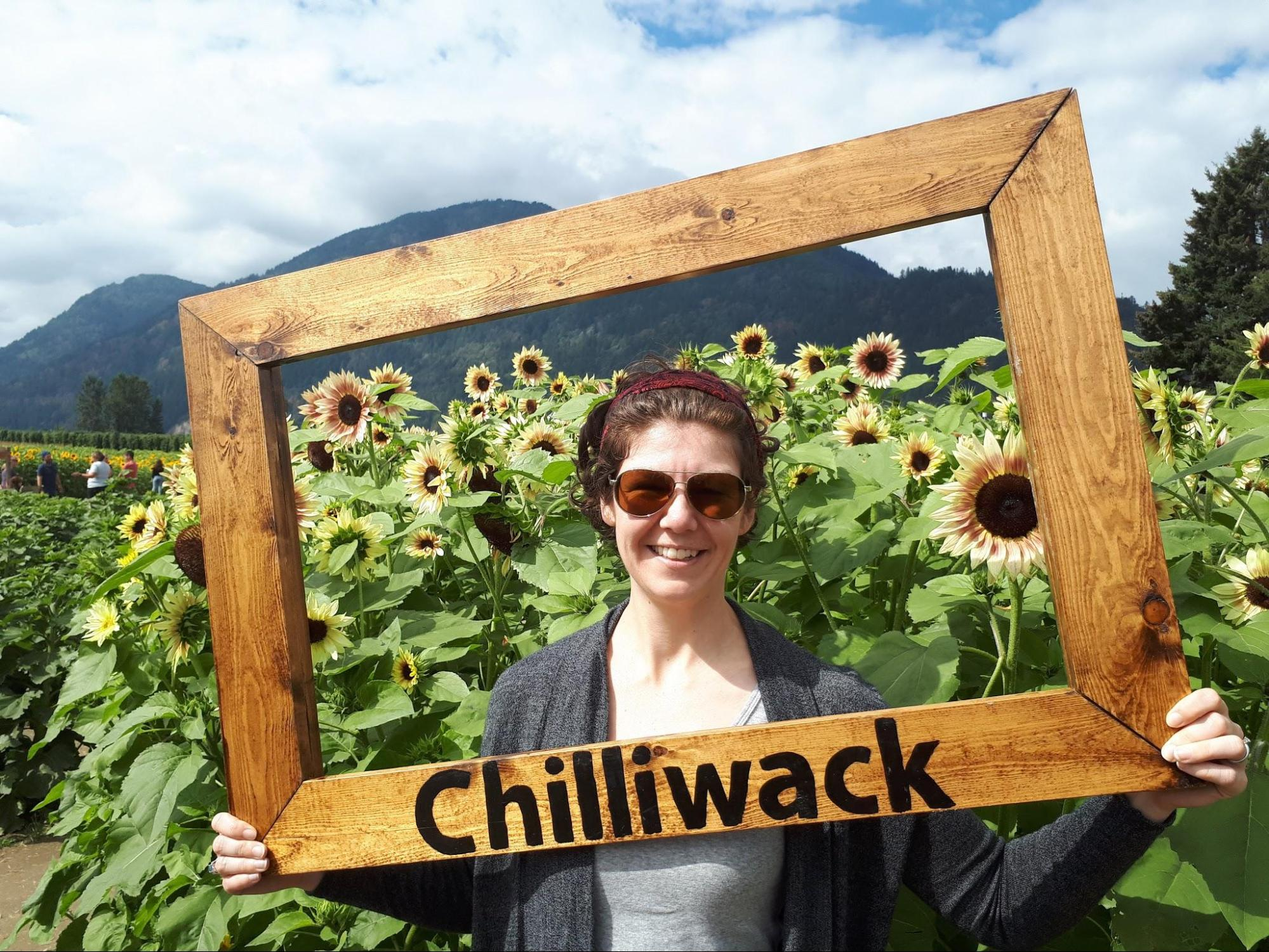 "Mel holding a large frame that says ""Chilliwack"" and standing in front of a field of sunflowers at the Chilliwack sunflower festival."
