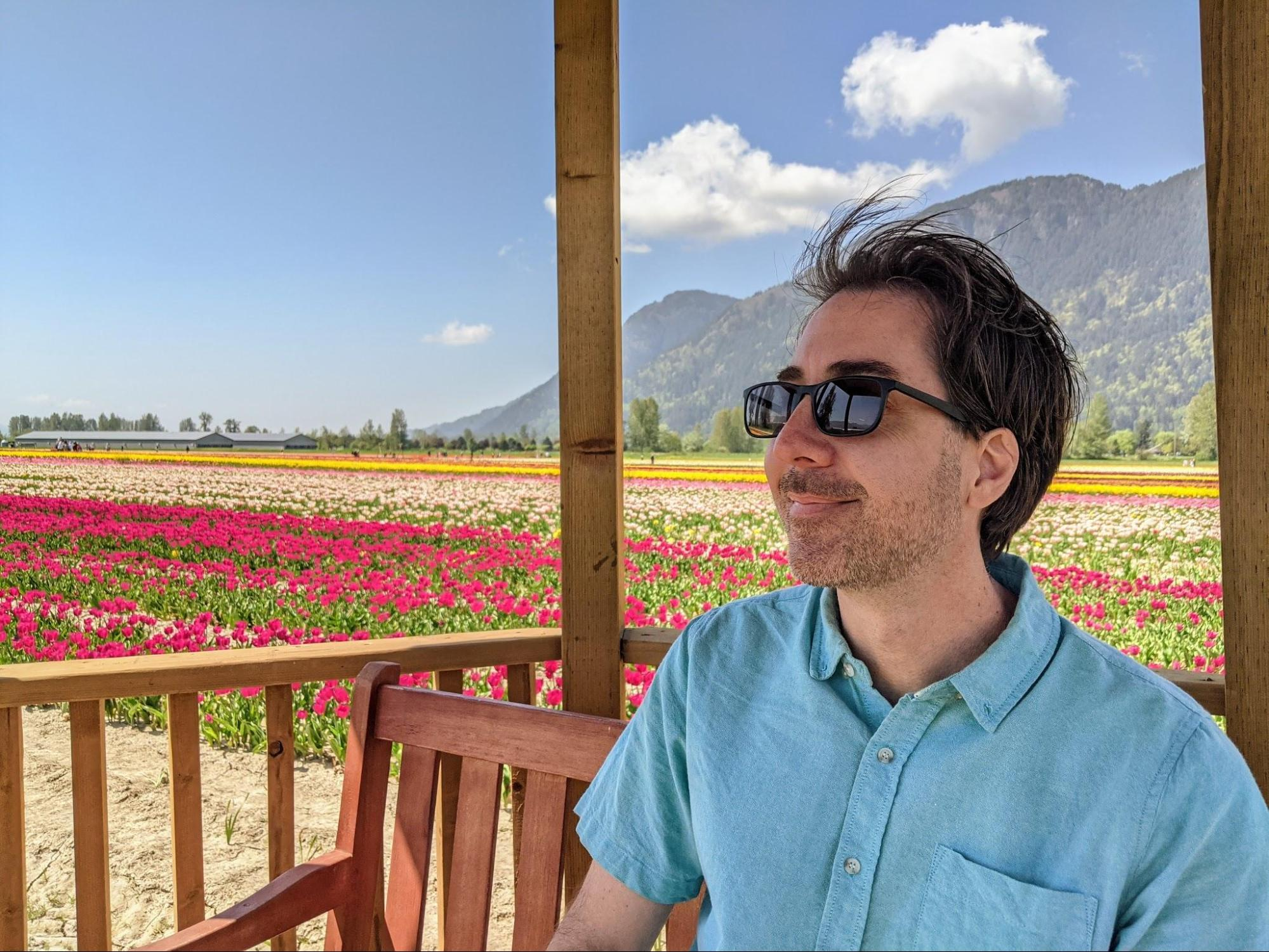 Jay sitting in a gazebo in front of the multi-colored field of tulips at the Chilliwack tulip festival